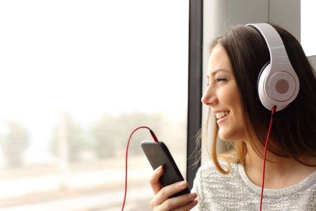 Happy teen passenger listening to the music traveling in a train and looking through the window